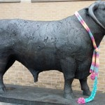 A statue of a bull, with a knitted scarf around its neck.