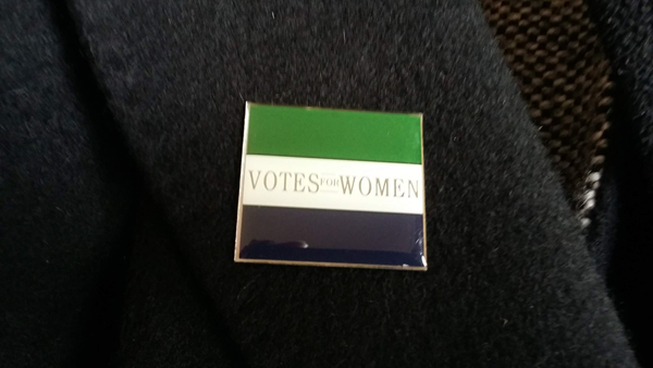 "Badge on a jacket lapel with the words ""Votes for women""."