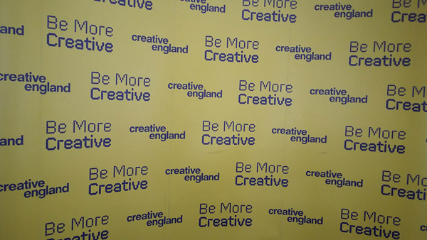 """A display banner with the words """"Be more creative"""" in a repeat pattern."""