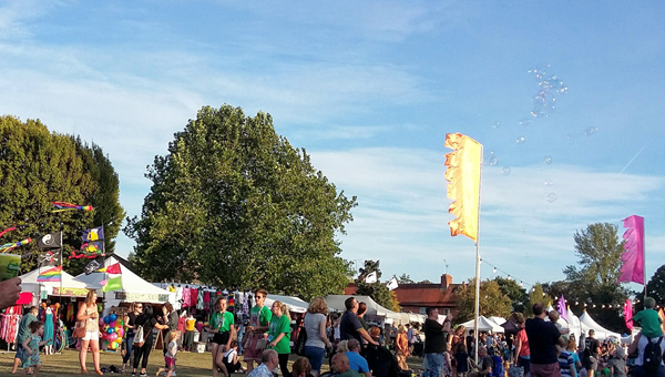 Wallingford Bunkfest: a festival atmosphere with families, flags and stalls in a park with a blue sky.
