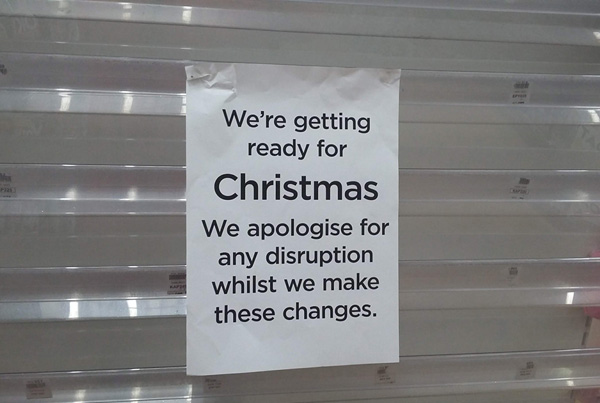 "A sign on an empty card rack in a shop: ""We're getting ready for Christmas. We apologise for any disruption whilst we make these changes."""