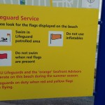 """Lifeguard Service"" poster on beach. Words include: ""RNLI Lifeguards and the 'orange' Seafront Advisors operate on this beach during the summer season. Lifeguards on duty when red and yellow flags are flying."""