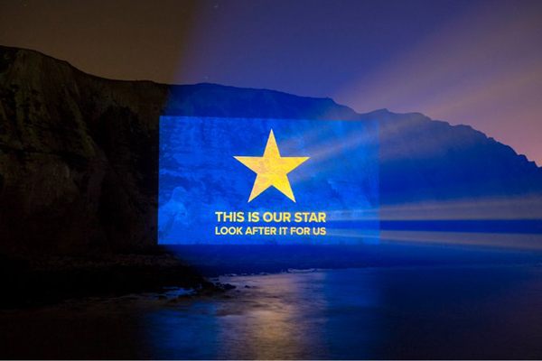 "Picture projected onto the white cliffs of Dover: a blue background with a single yellow star and the words ""This is our star. Look after it for us."""