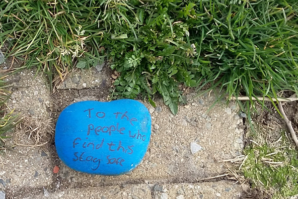 """Pebble on the ground, painted blue with the message: """"To the people who find this, stay safe."""""""