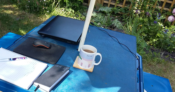 A picnic table in a garden, with a laptop, notebook and coffee mug on it.